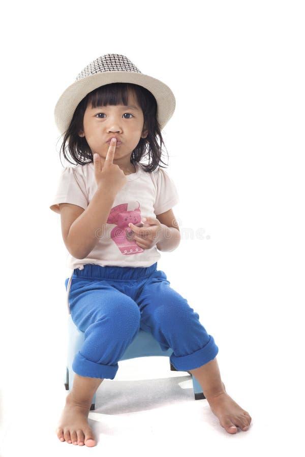 坐和盖嘴的女孩 免版税库存照片