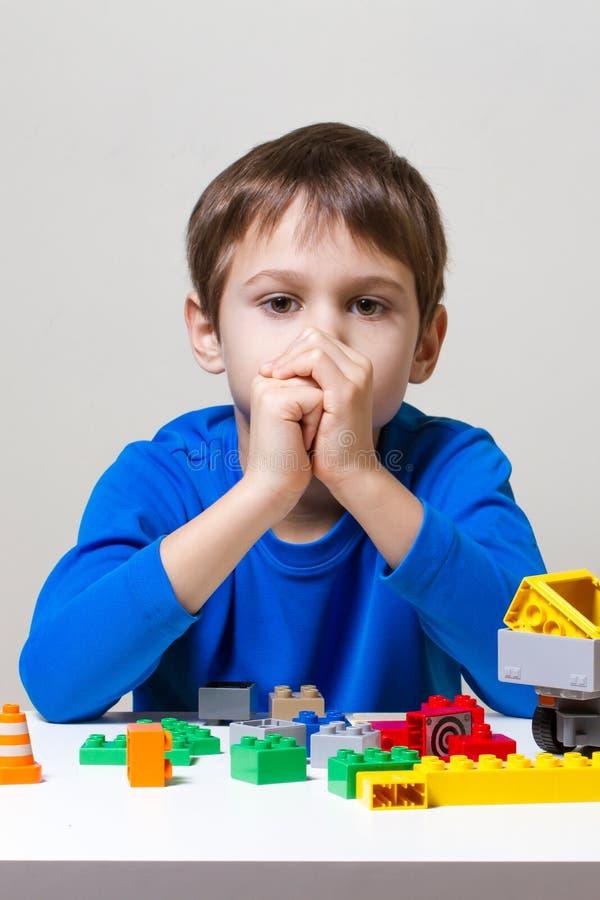 坐和看对五颜六色的塑料建筑玩具块的疲乏的不快乐的孩子桌 免版税库存照片