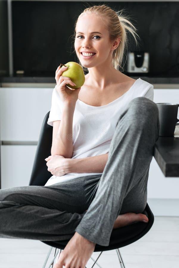 坐和看照相机的白肤金发的夫人画象在厨房里 免版税库存图片