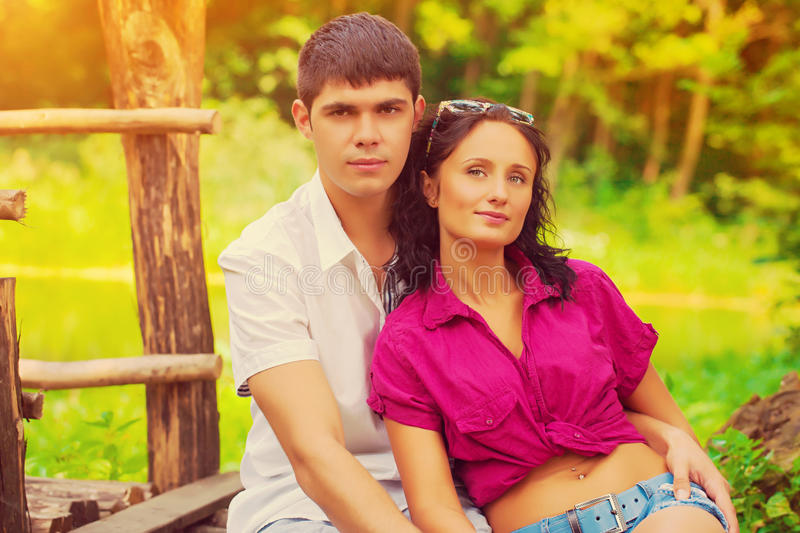 坐和看照相机的年轻美好的夫妇画象  库存照片