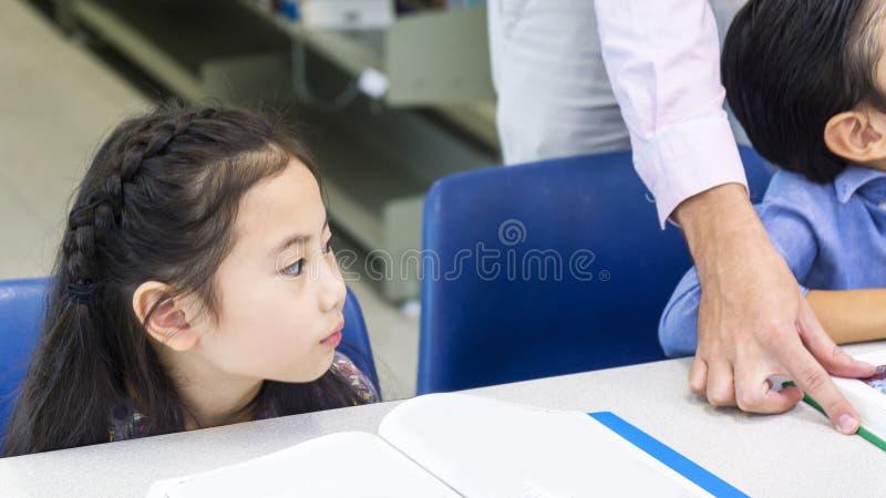 坐和看见朋友孩子的亚裔逗人喜爱的女孩 库存照片