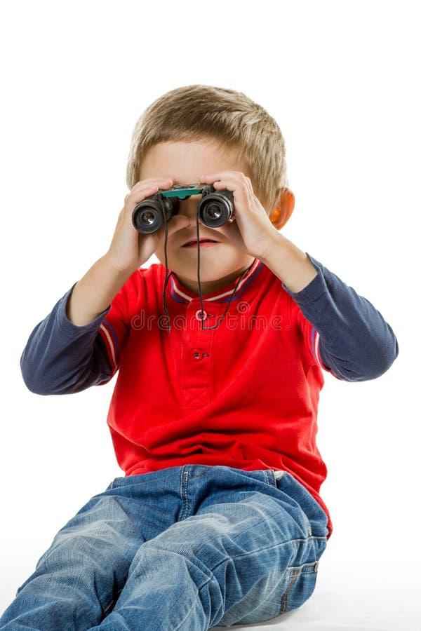 坐和看通过双筒望远镜的男孩 图库摄影
