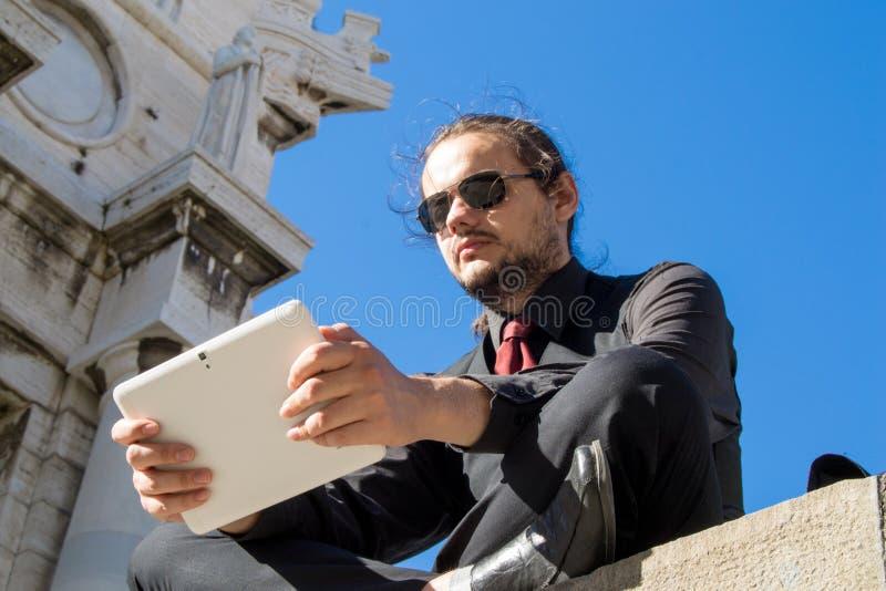 坐和看他的计算机的年轻绅士 免版税图库摄影