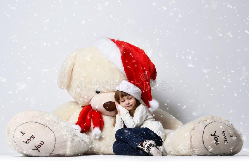 坐和睡觉与在圣诞节圣诞老人红色帽子的大软的玩具熊玩具的女孩在大雪下 免版税图库摄影