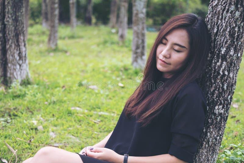 坐和睡觉由树的亚裔妇女有绿色森林背景 图库摄影