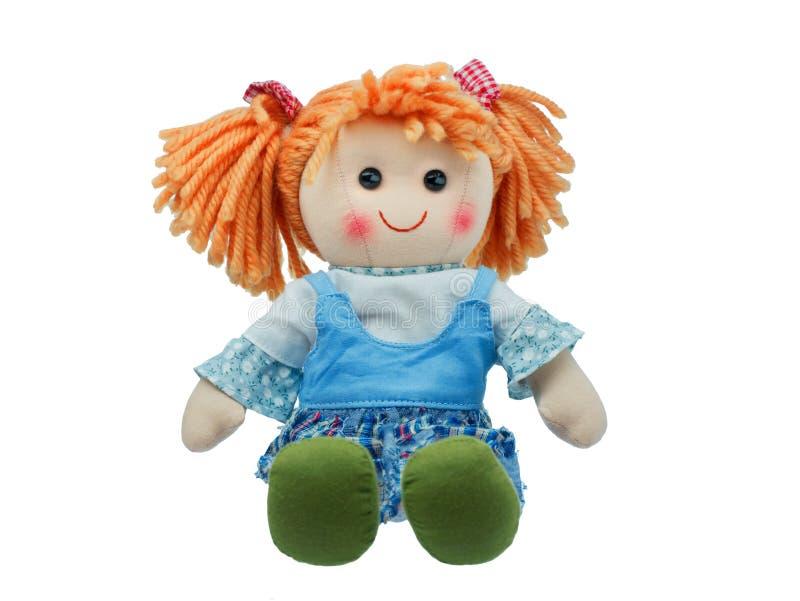 坐和被隔绝的微笑的逗人喜爱的布洋娃娃 库存图片