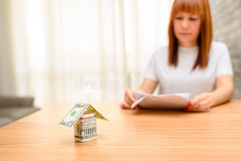 坐和计算票据的愉快的妇女在家庭办公室 从美元钞票的金钱房子在木桌上 图库摄影