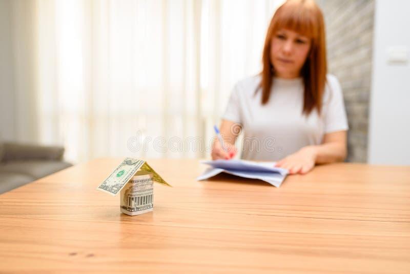 坐和计算票据的愉快的妇女在家庭办公室 从美元钞票的金钱房子在木桌上 免版税库存图片