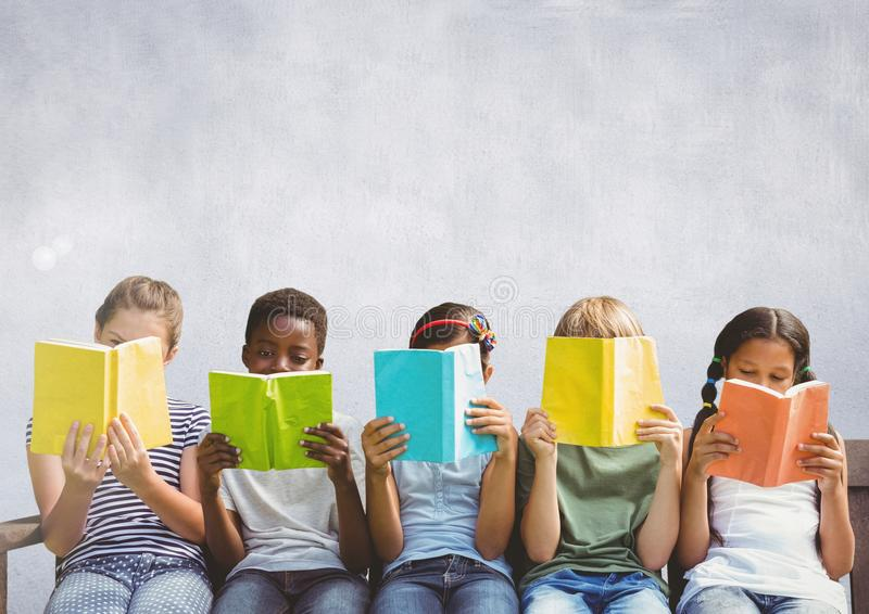 坐和读在灰色背景前面的小组孩子 免版税库存图片