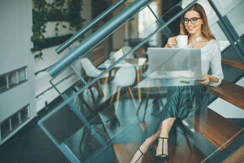 坐哦办公室台阶的俏丽的女实业家,有咖啡休息和网冲浪互联网 免版税库存图片