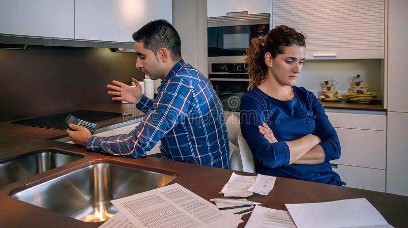 坐回到彼此的恼怒的夫妇在争吵以后由债务 免版税图库摄影