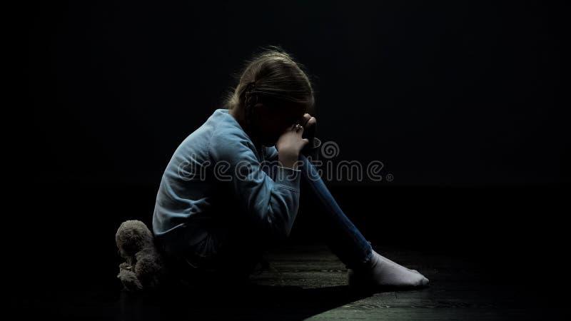 坐回到玩具熊的哭泣的女孩在黑暗的被放弃的室,寂寞 免版税库存照片