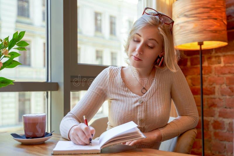 坐在一个咖啡馆的一张桌上的庄严可爱的女实业家与一杯咖啡和笔记本 免版税图库摄影