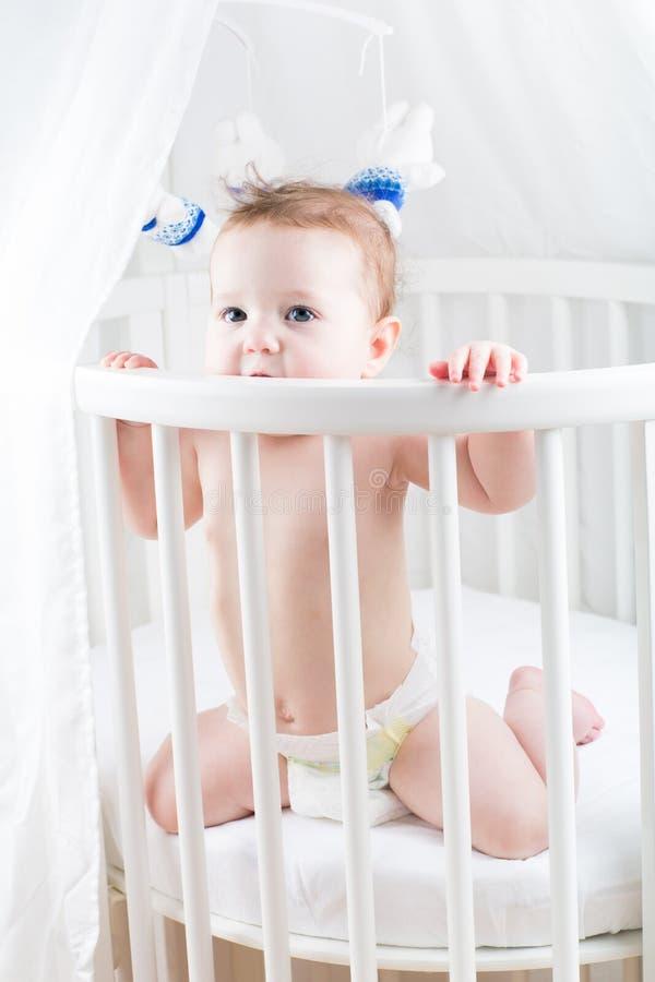 坐在一个圆的白色小儿床的滑稽的婴孩 库存照片