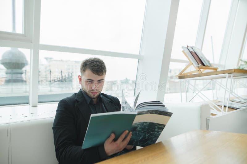 坐在一个时髦的现代咖啡馆的窗口和读杂志的一个英俊的有胡子的人 免版税图库摄影