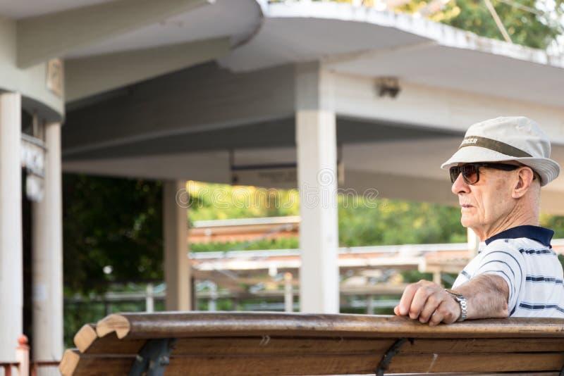 坐在一个火车站的一名老人在希腊 库存图片