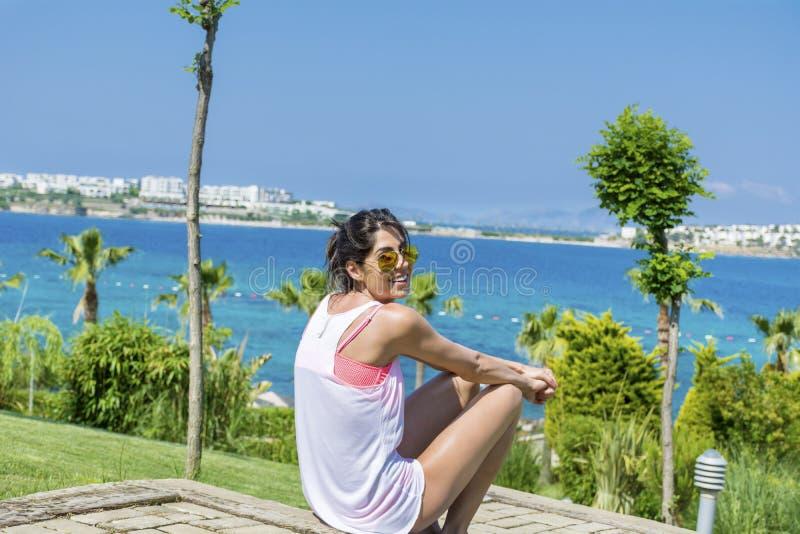 坐在一个热带海庭院里的少妇画象 免版税图库摄影