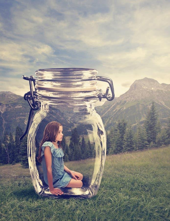 坐在一个玻璃瓶子的女孩 图库摄影