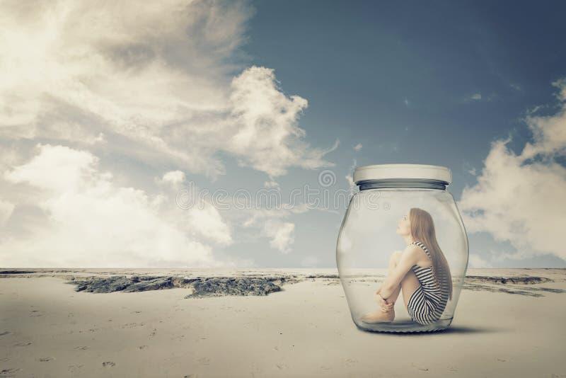 坐在一个瓶子的少妇在沙漠 寂寞外围之物概念 免版税库存照片