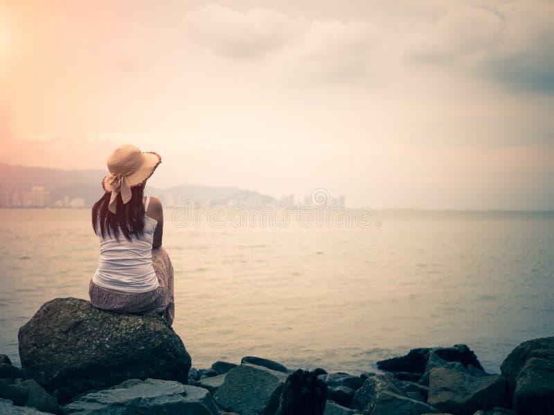 坐在一个离开的海滩的海前面的孤独和沮丧的妇女减速火箭的样式  免版税库存图片