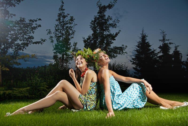 坐在一个美丽的庭院里的二个微笑的女孩 免版税库存图片