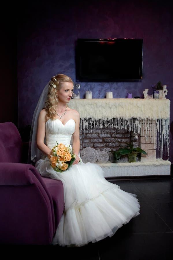 坐在一个装饰蜡壁炉的婚礼礼服的新娘 免版税库存图片