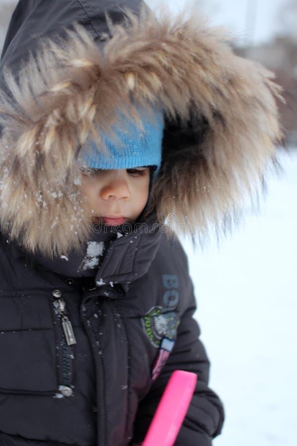 坐在一个雪撬的衣服暖和的小男婴在雪皱眉的冬天结冰不要走 免版税库存照片