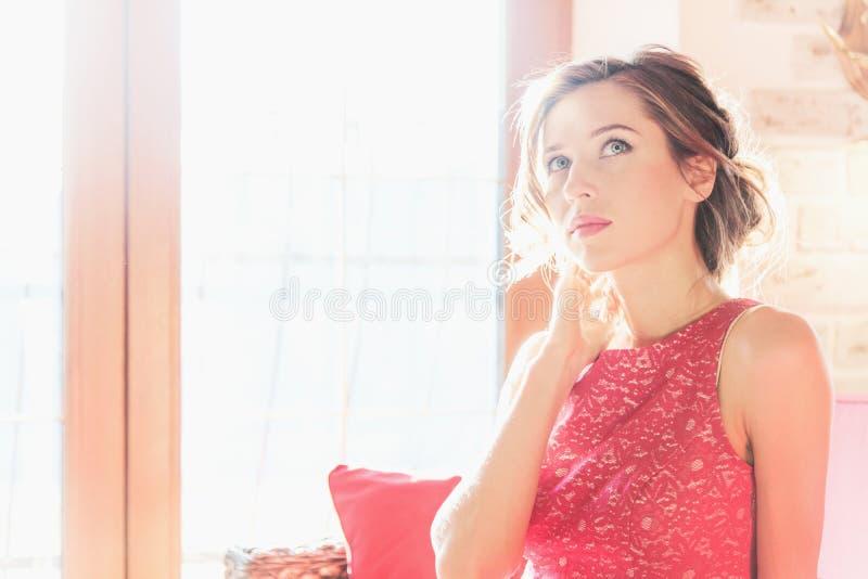 坐在一个晴朗的窗口附近的美丽的深色的妇女 库存图片