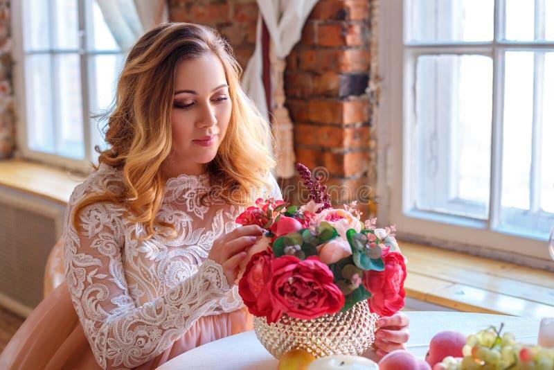 坐在一件美丽的礼服,母性的概念的桌上的孕妇 免版税库存图片