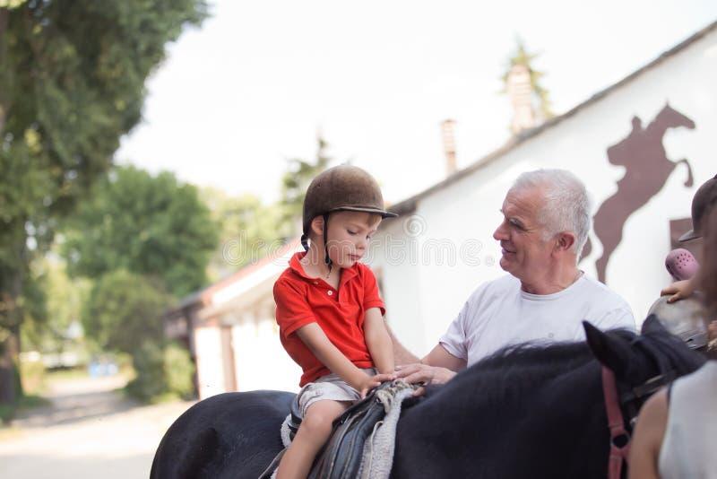坐在一匹黑马顶部的男孩听他的grandfather& x27; s指示 免版税库存照片