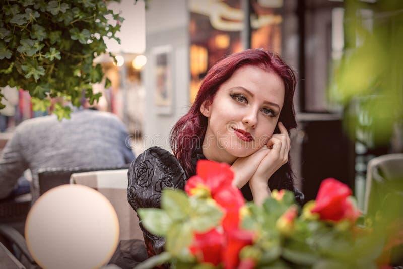 坐在一室外咖啡馆dresse的年轻华美的红发妇女 免版税库存照片