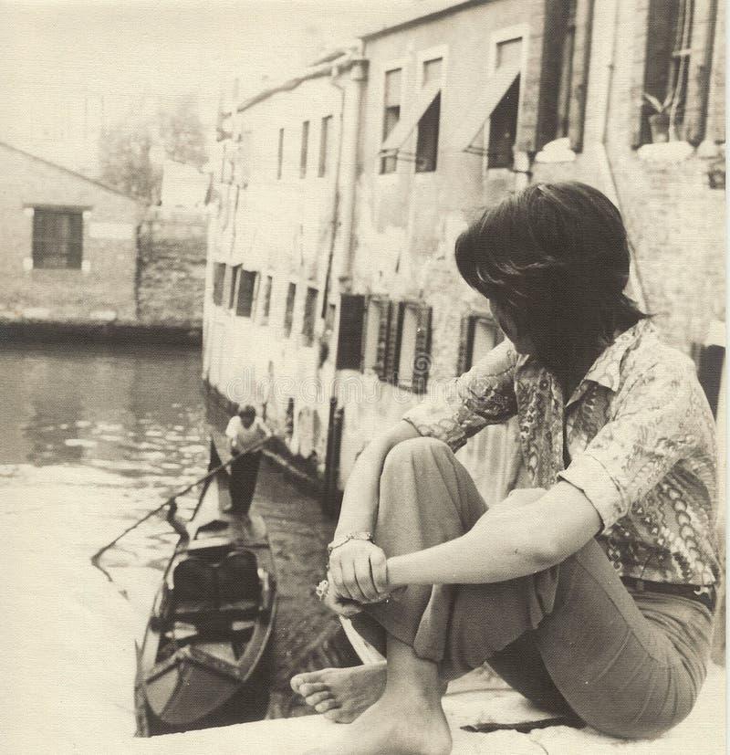坐在一座桥梁一边的女孩在观看一张长平底船通行证,20世纪60年代的威尼斯 免版税库存图片