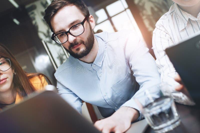 坐在一张木桌上和工作在lapt的小组工友 免版税库存照片
