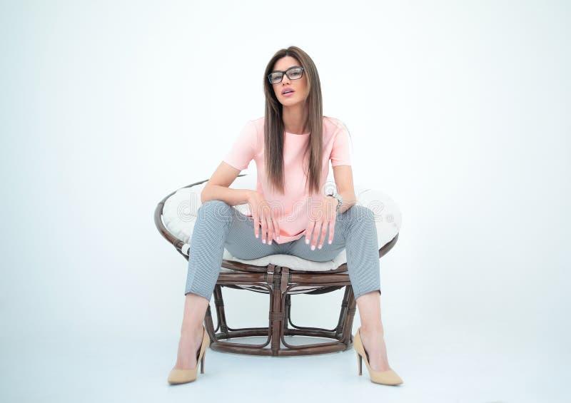 坐在一把圆的椅子的现代少妇 库存图片