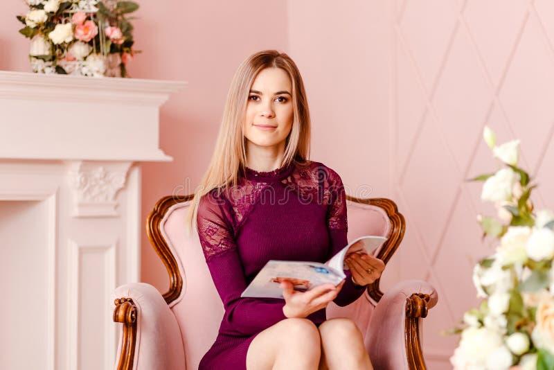 坐在一把桃红色椅子和拿着杂志的20岁的美丽的微笑的妇女 免版税库存图片