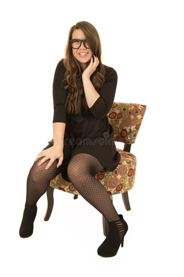 坐在一把花卉椅子的更加年轻的女性模型 免版税库存图片