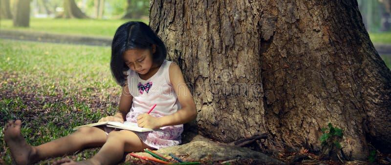 坐在一棵大树下和写书的小女孩 免版税库存照片