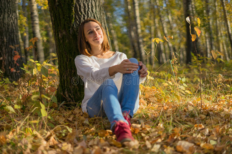 坐在一棵树下的女孩在秋天森林里 免版税库存图片