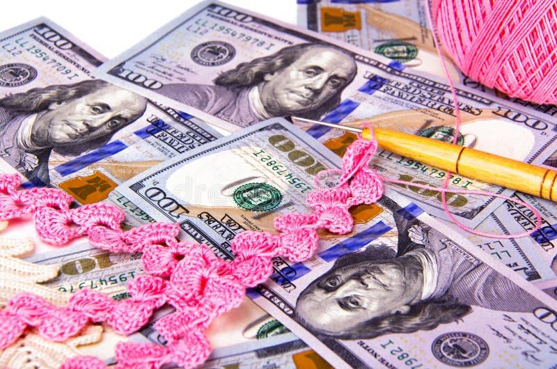 坐在一百元钞票顶部的钩针编织针和手工制造鞋带 免版税库存照片