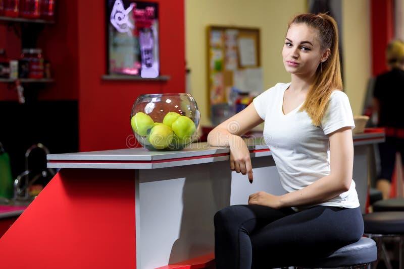 坐在一碗的女孩在健身房的苹果附近 免版税库存照片