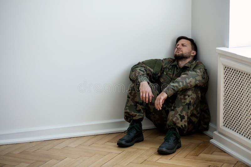 坐在一间空的屋子的角落的制服的沮丧的军队人 您的海报的地方墙壁的 库存照片