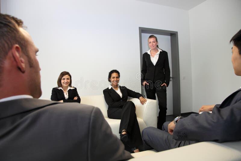 坐在一间候诊室的时髦的商人 库存照片