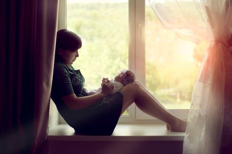 坐在与一个新出生的婴孩的窗口的少妇母亲 库存照片