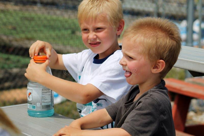 坐在与一个瓶的一张桌上的两个年轻男孩Gatorade 免版税图库摄影