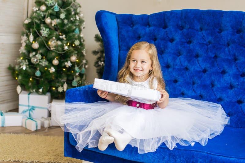 坐在与一件新年的礼物的圣诞树附近的女孩 免版税库存照片