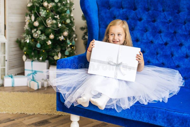 坐在与一件新年的礼物的圣诞树附近的女孩 免版税库存图片