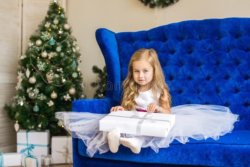 坐在与一件新年的礼物的圣诞树附近的女孩 库存图片