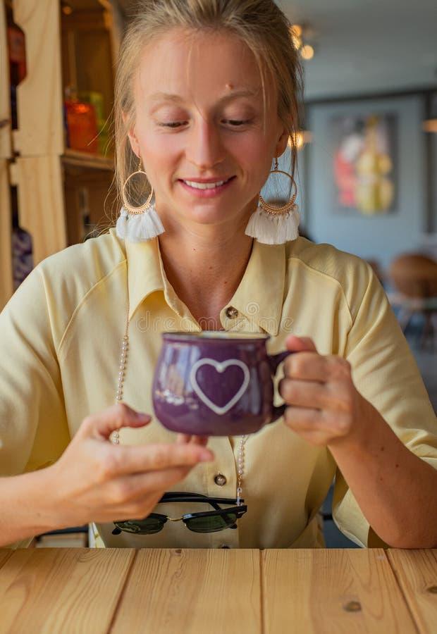 坐在与一杯咖啡的一个咖啡馆的美女 可爱的年轻女人喝咖啡或热奶咖啡 库存图片