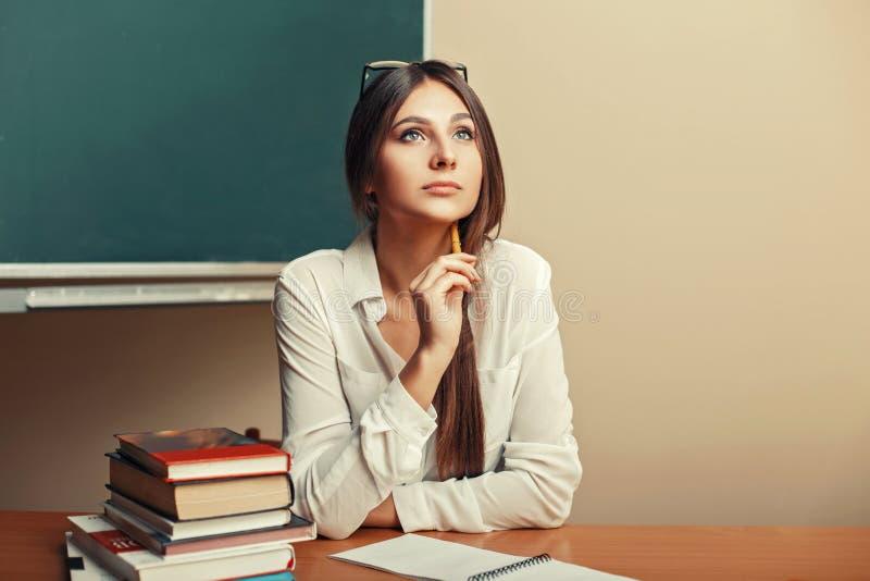 坐在与书的桌上的美丽的少妇 免版税图库摄影