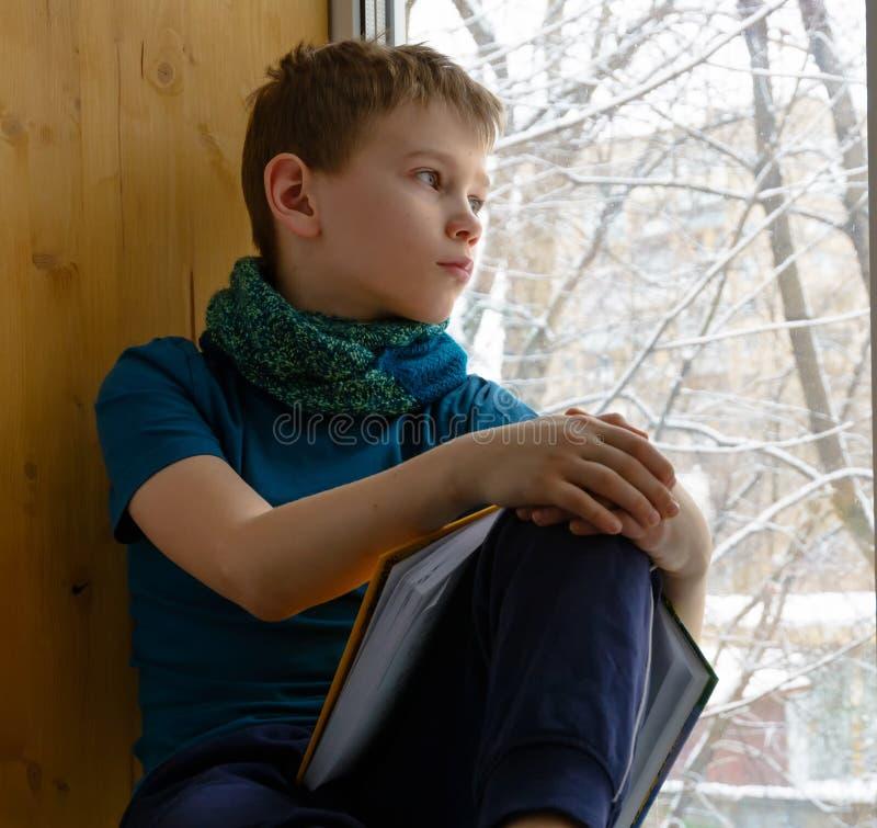 坐在与书的窗口附近和看在冬日的男孩,户内 库存图片